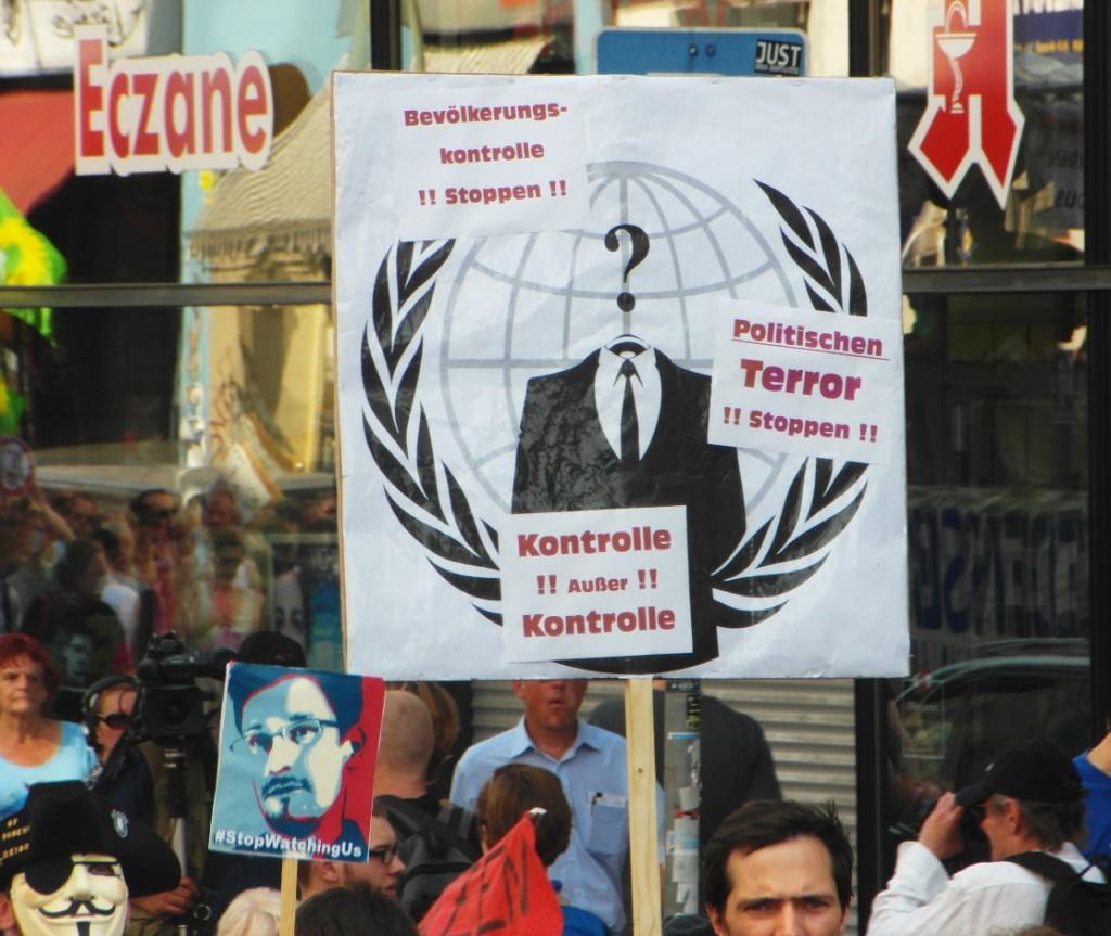 Abb. 12: StopWatchingUs Demo Berlin 2013 — Anonymous, Bevölkerungskontrolle stoppen, politischen Terror stoppen, Kontrolle außer Kontrolle.