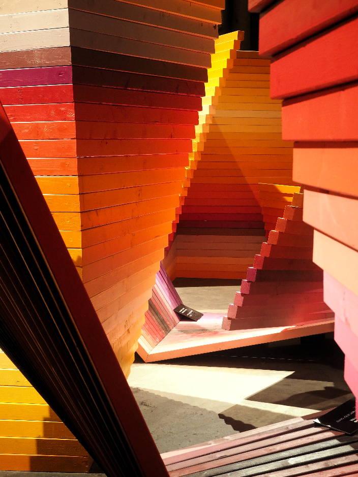 Begehbare Holzlatteninstallation in Regenbogenfarben.