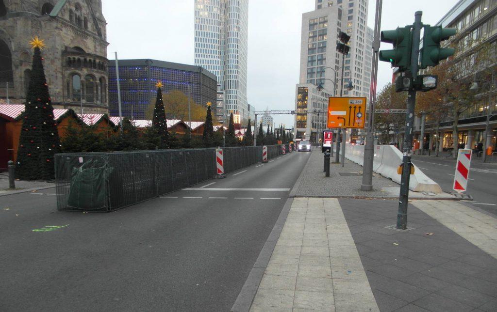 Von links nach rechts: Weihnachtsmarktbuden, noch mit Sandtaschen zu bestückende Gitterkörbe, verbleibender Fahrstreifen, mittige Betonsperre.