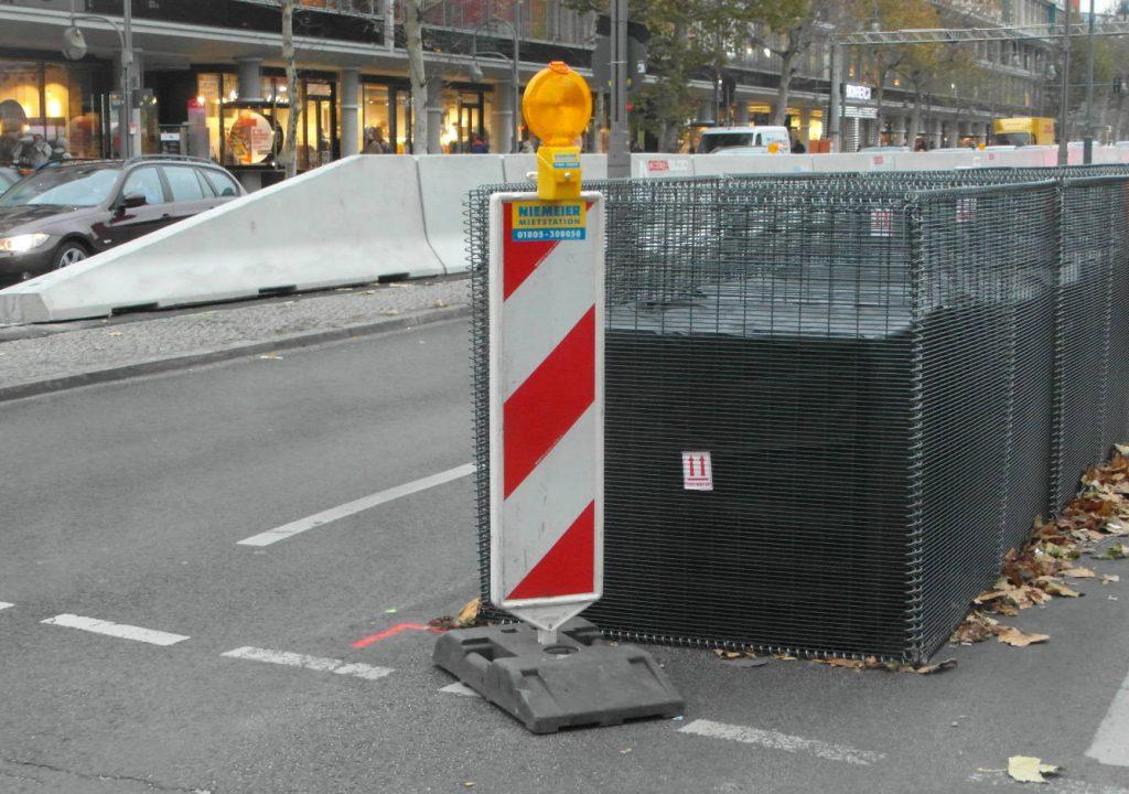 Befüllter Gitterkorb und Betonsperren.